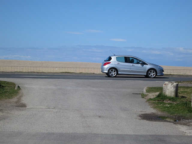 Silver car being driven along the causeway between Portland and Weymouth with Chesil Beach in the Background