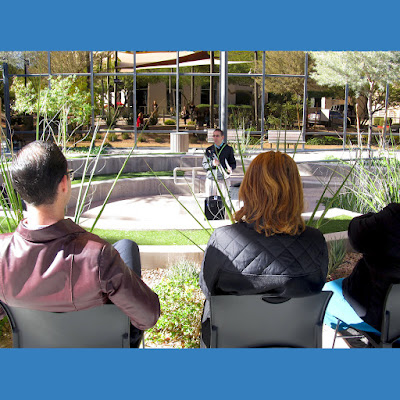 "The back of Rio staff members' heads in the foreground as they listen in to Associate Dean and trumpet player Dustin Maroney perform in the background during ""Lunch Break at Rio"""