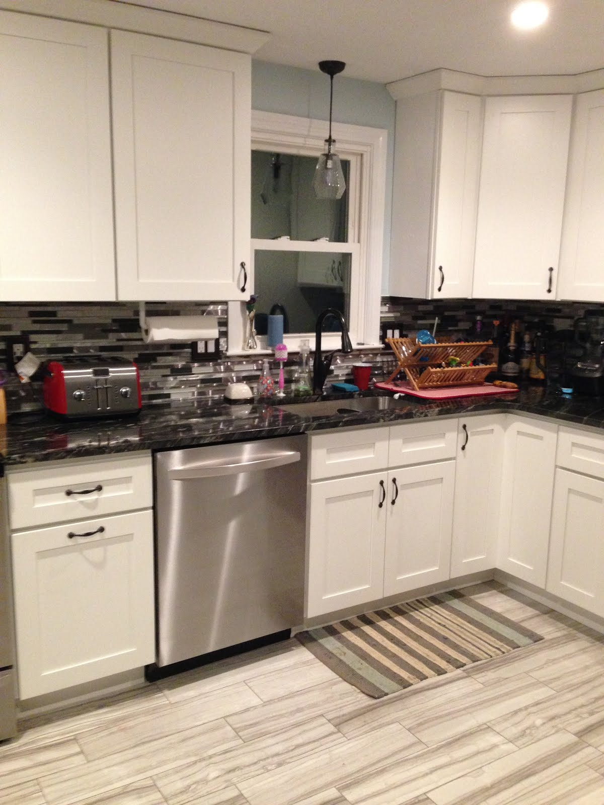 updated kitchen with white cabinets, black countertops, and stainless steel appliances