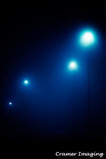 Cramer Imaging's professional quality fine art photograph of four blue-toned street lights in the dark and fog of Pocatello, Bannock, Idaho