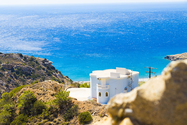 Stock photo of the View of the coast of Crete with a pale blue house in front of the sea