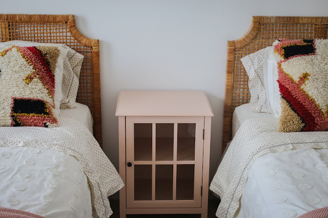 Rattan Headboards, boho pillows, and a pink side table