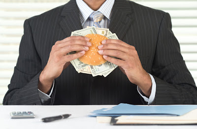 A photo of a business man holding a burger stuffed with money.