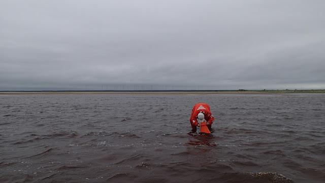 Pelastautumispukuinen henkilö katsoo vesikiikarilla veden alle matalassa vedessä