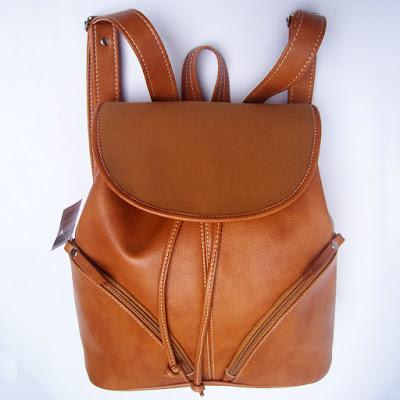 Mochila con bolsillos curvos y tapa combinada con agamuzado al tono.