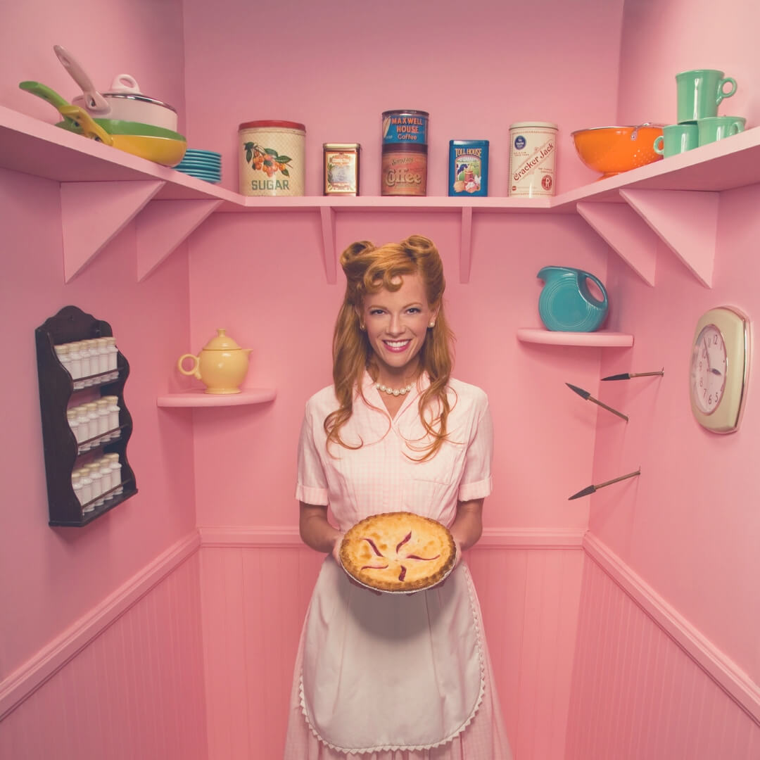 Why It's Okay To Be A Stay-at-home Mum When You're Not A Natural Homemaker | woman dressed in 50s outfit with pearls around her neck, she is holding a pie and smiling.