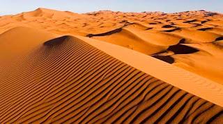 Bukit di luar Merzouga di jantung Sahara lebih tinggi dari yang Anda bayangkan. Naik 150 meter di beberapa tempat, tumpukan memabukkan peach berwarna pasir membuat lautan kurva sensual, memanggil Anda untuk naik. Tapi mendaki bukit pasir adalah keterampilan, terutama di pasir Sahara longgar dikemas, di mana dua langkah yang diikuti oleh satu langkah ke bawah. Jika Anda membuat itu, jika Anda menaklukkan gundukan dan berdiri penuh kemenangan di puncak, Anda akan melihat bermil-mil dari kekosongan, dan Anda akan merasakan ketenangan luhur merangkul jiwa Anda, untuk dunia hanya berhenti untuk Anda.
