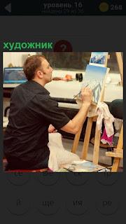 на улице сидит художник с мольбертом и пишет свою картину