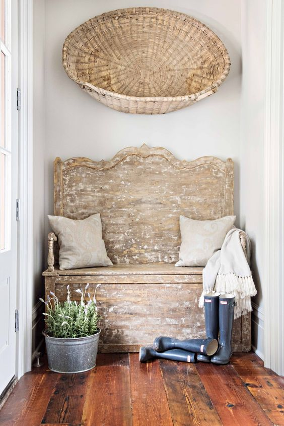 A Rustic And Weathered Wood Farmhosue Bench With Pillows Galoshes Lavender