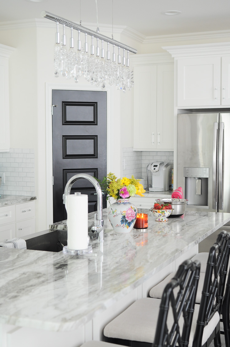 Colorful accessories really liven up this chic and beautiful bright white kitchen with black pantry door.