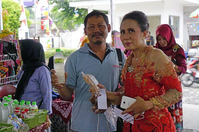 Pak Wiwit memegang sari lidah buaya, dan ibu menunjukkan Gula Jawa