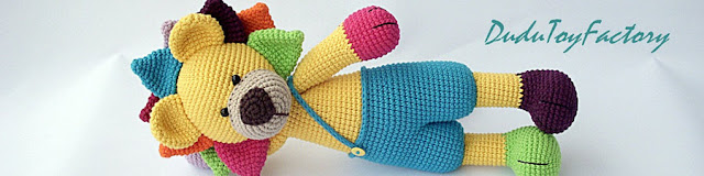 Colorful crochet amigurumi lion lying down