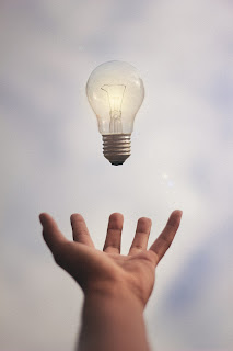 A hand reaching out to catch an airborn incandescent lightbulb