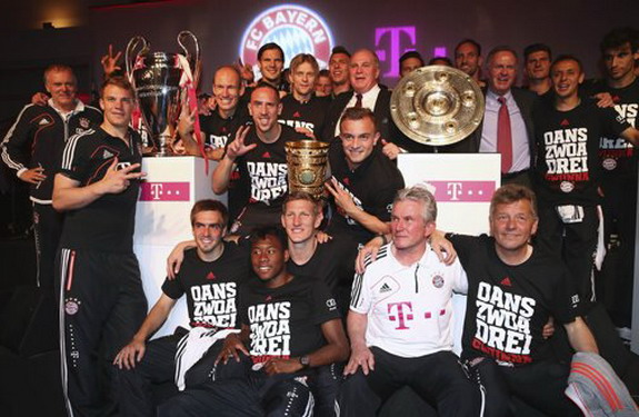 Bayern Munich team pose with their Champions League, DFB Pokal, and Bundesliga trophies