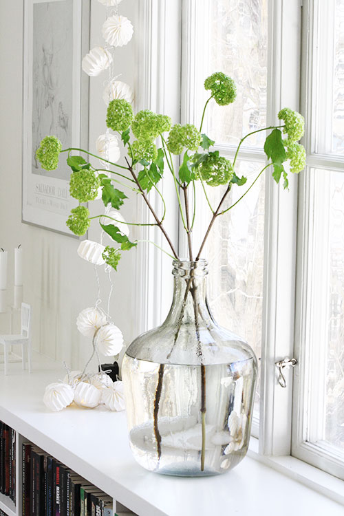 green blooms glass vase white room