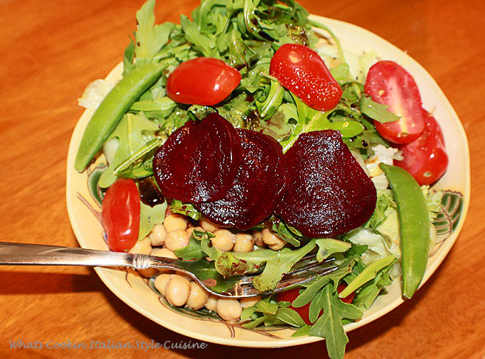 These are beets in a healthy salad with tomatoes, snap peas, chickpeas, arugula, romaine, cucumbers, with olive oil and 18 year aged balsamic vinegar