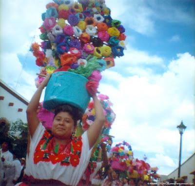 mujer con canasto de flores en guelaguetza
