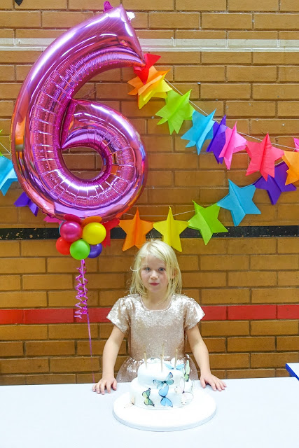 My daughter at her 6th birthday party standing in front on a helium number 6 and behind a Marks and Spencer butterfly cake