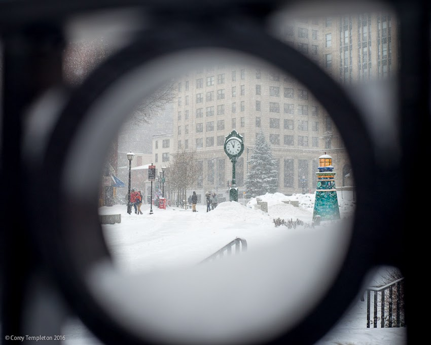 Portland, Maine USA December 2016 photo by Corey Templeton. Looking through a fence outside of One City Center towards Monument Square like a snow globe.