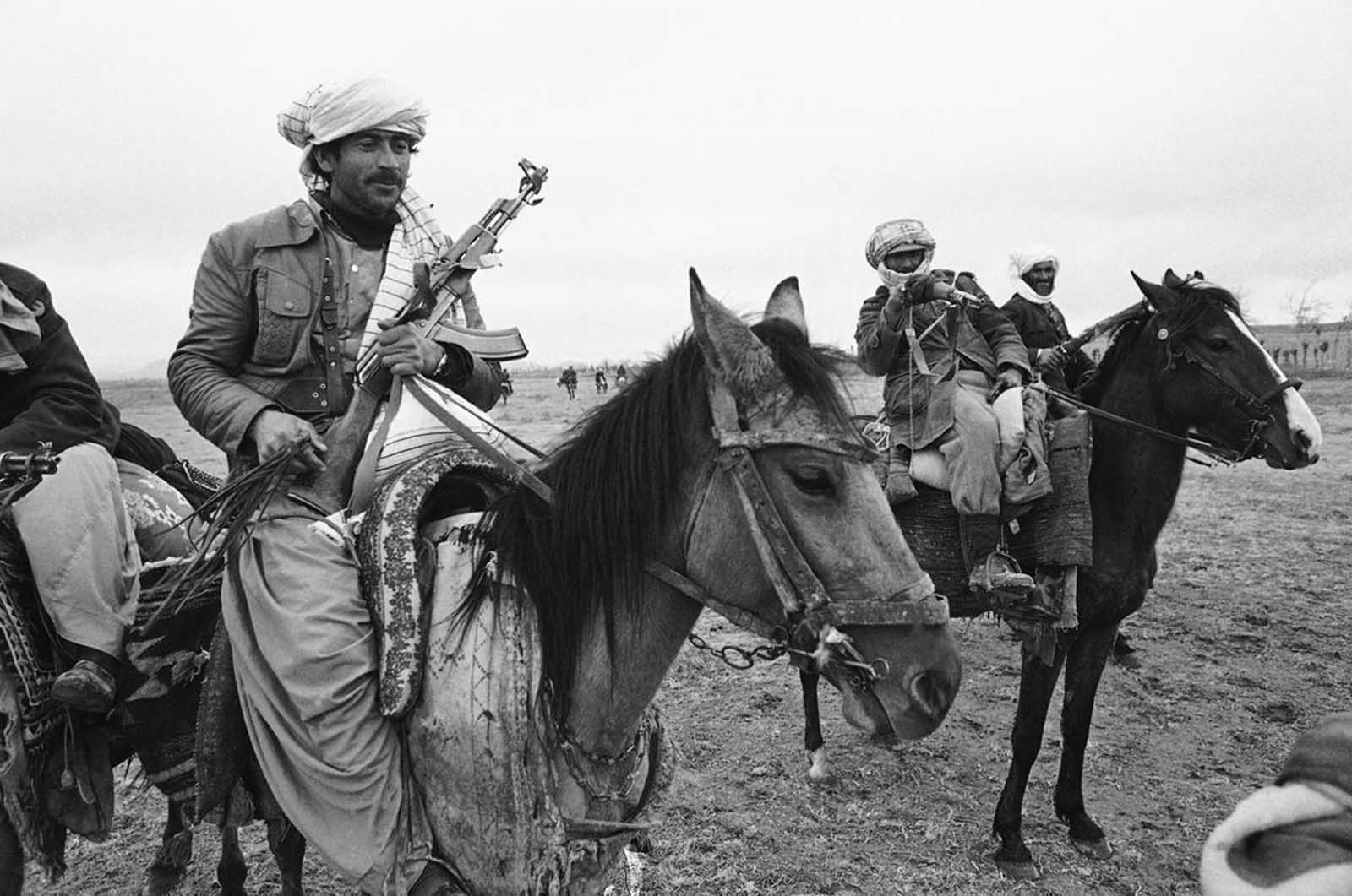 Three Muslim rebels, one armed with a Soviet-made AK-47 assault rifle, left, the others with older bolt-action rifles, pose on horseback during a rebel meeting at village near Herat, on February 15, 1980. Despite the presence of Soviet and Afghan government troops in the area, the rebels patrolled the mountain ranges along the Afghan-Iran border.