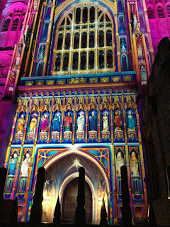Pic of frontage of Westminster Abbey lit up in pink and other colours