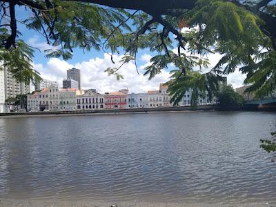 Fotografia colorida. Em primeiro plano, o rio Capibaribe e galhos de uma árvore à beira do rio. Ao fundo, o casario colorido da rua da Aurora  e o céu azul com nuvens brancas.