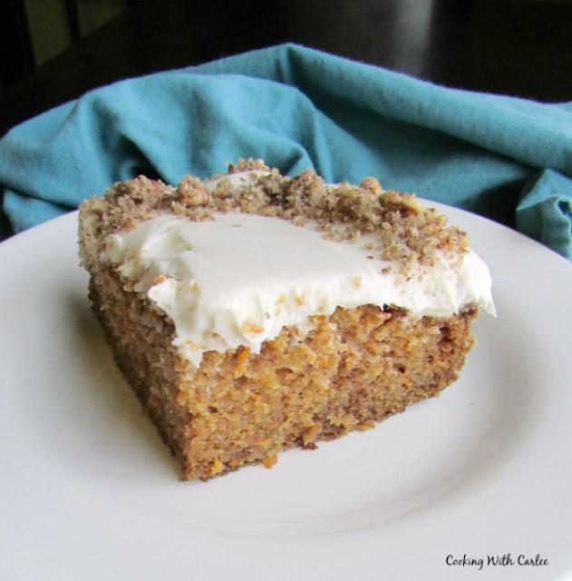 piece of carrot cake with cream cheese frosting and graham cracker crumbs