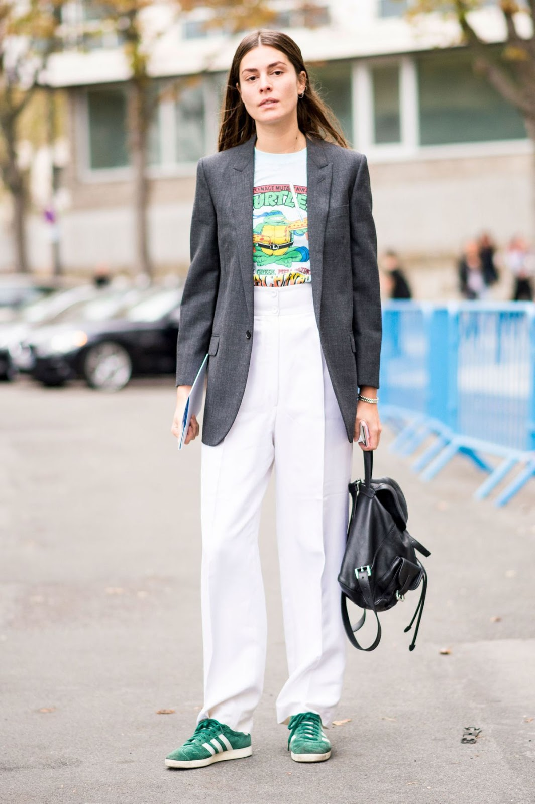 Cool Spring Street Style Outfit — Grey Blazer, Graphic T-Shirt, White Pants, Black Backpack, and Green Adidas Sneakers
