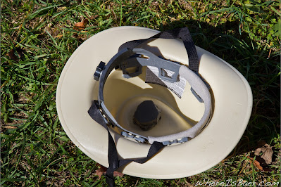 inside of kahki cowboy helmet sitting on grass