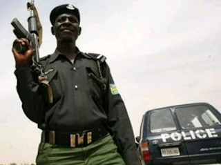 nigerian policeman with a gun standing with a police car behind him