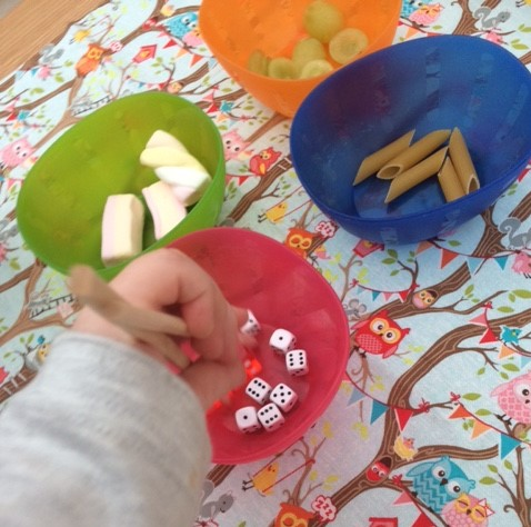 Toddler using the chopsticks with the bowls