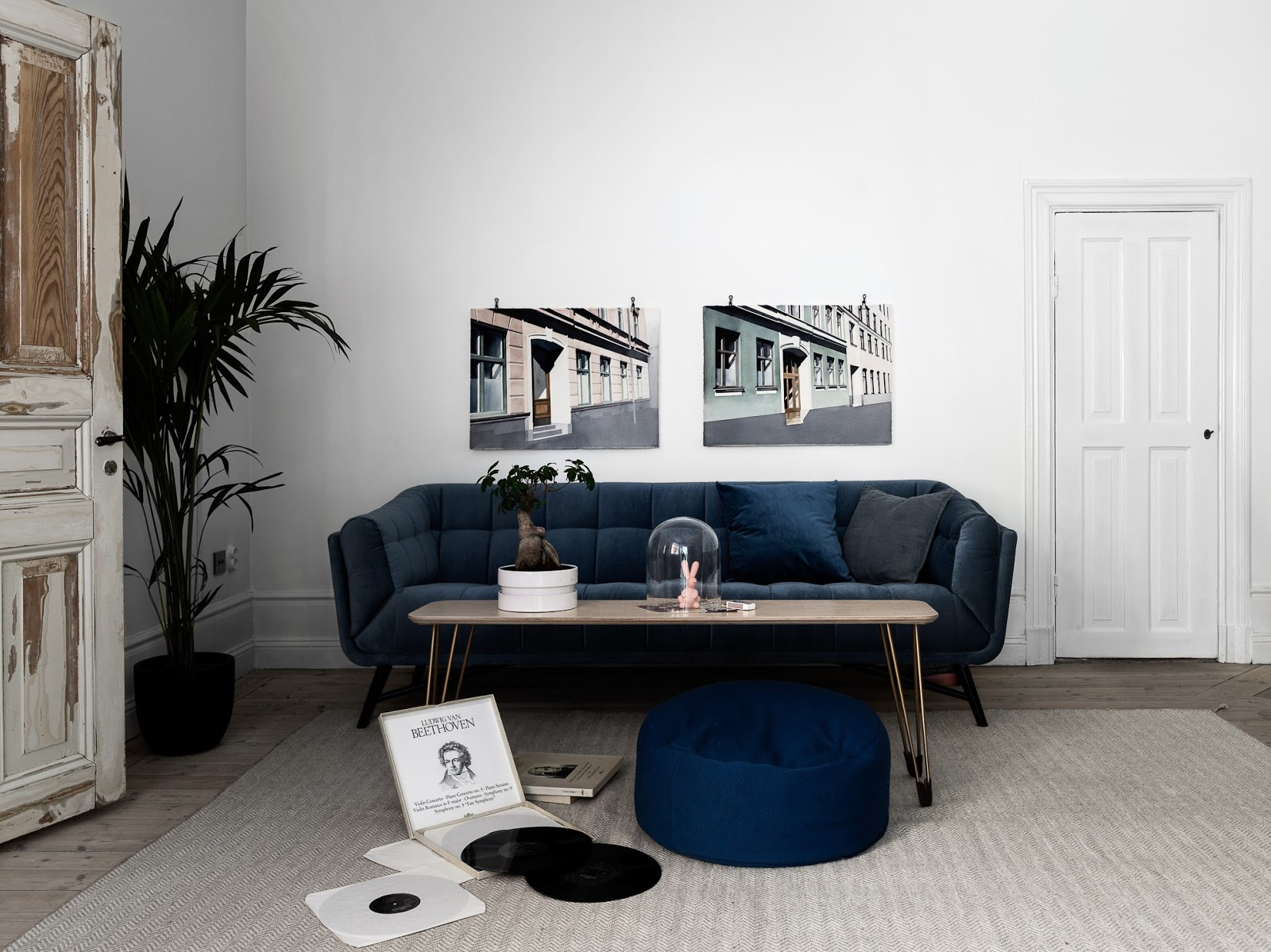 high ceilings apartment with wooden floors, white painted walls, danish design, blue sofa