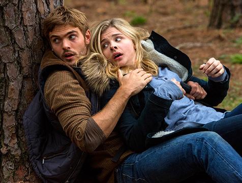 Evan Walker (Alex Roe) y Cassie Sullivan (Chlöe Moretz) ocultándose en La quinta ola - Cine de Escritor