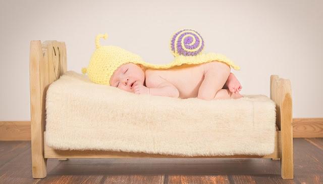 foto bayi lucu yang sedang tidur di atas ranjang mungil