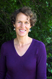 Photo of Dr. Jennifer Skuza wearing a purple shirt standing outside in front of a bushy green background
