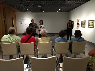 En la sala de la Fundación Cajasol, los organizadores hablan al público oyente que permanece sentado, mientras que una intérprete en lengua de signos trasmite la información a las personas sordas signantes.