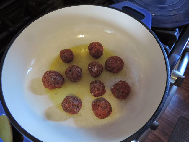The meatballs browning in the pan.
