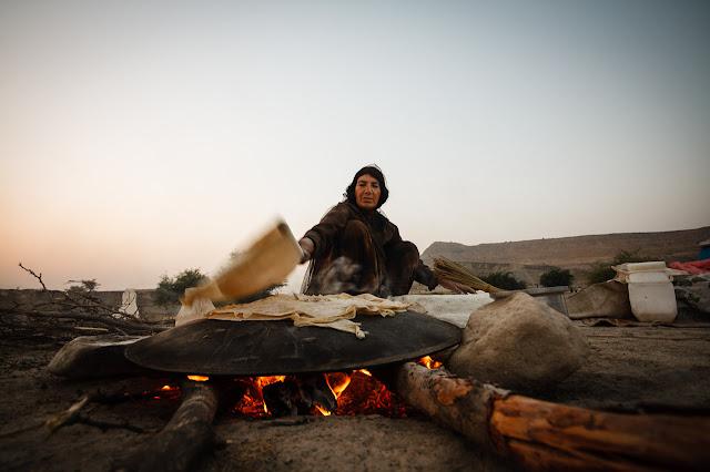 Mujer nómada haciendo pan al fuego