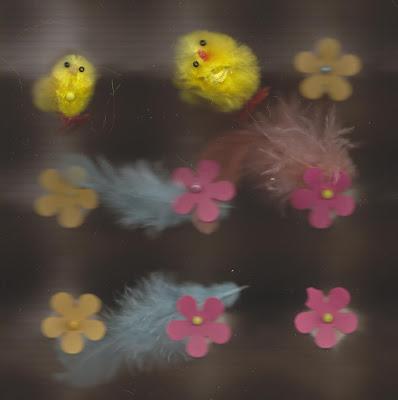 Kuvassa on kaksi tipua, höyheniä ja kukkia. Kukat ovat punaisia ja keltaisia. Höyhenet ovat sinisiä. Tiput ovat keltaisia. Toinen tipu on pää kallellaan. Tausta on musta. Kuva on tehty skannaamalla kolmiulotteista materiaalia.