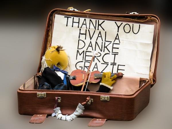 Imagem de uma mala com um violino e um cartaz de agradecimento