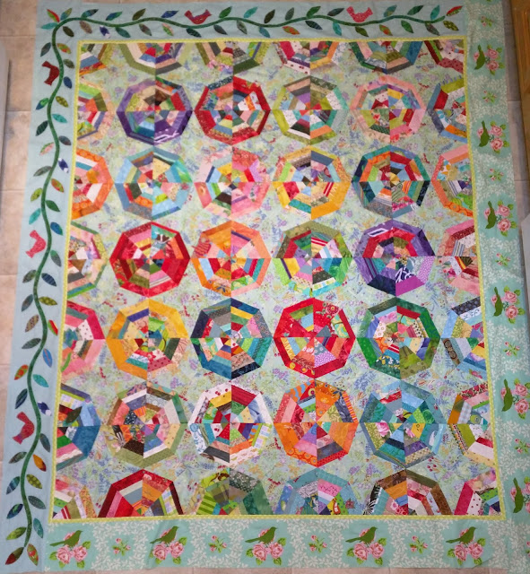 Cardinals sit on a leafy vine border around two sides of this scrap spiderweb quilt.