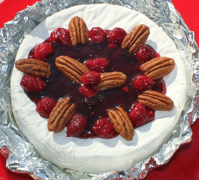 this is an appetizer made with brie, raspberries and pecans