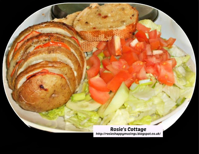 Extra yummy Hasselback baked potato loaded with slices of mozzarella cheese and tomato, served with a crunchy salad and garlic bread.