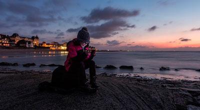 Mujer sonriente con un smartphone en la playa