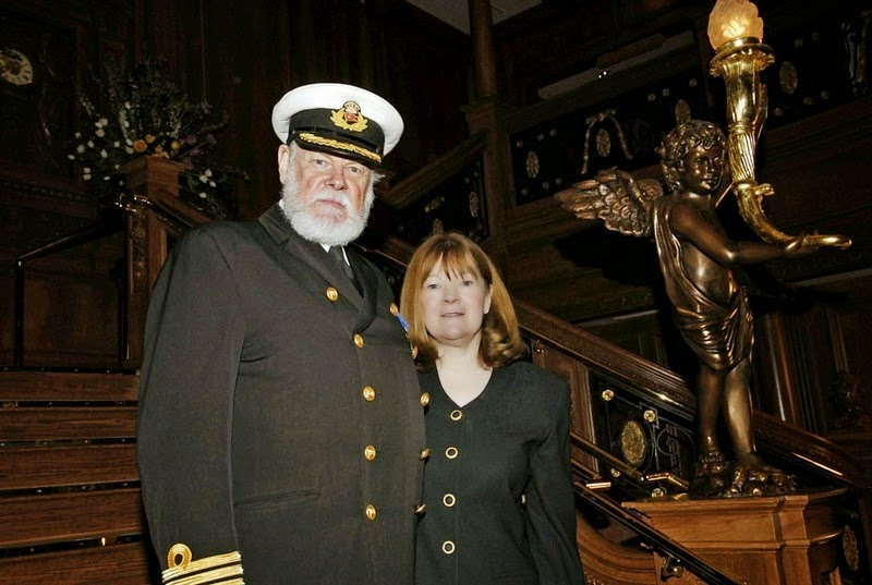 An actor dressed as the ship's Captain poses with a visitor for a photograph. - The Titanic Museum in Branson
