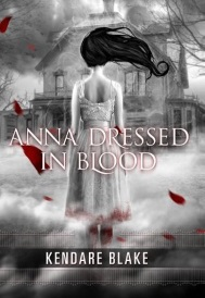 Cover of Anna Dressed In Blood, rendered in shades of white and grey with scattered red leaves falling diagonally across the composition. A white-skinned girl with stark black hair that blows straight out to the side to expose her neck faces a large, ruined house. Smoke swirls around her. She wears a sleeveless white dress with a hint of red on its knee-length hem.