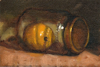 Oil painting of a lemon in a glass jar--laid on its side--with a gold-coloured lid.
