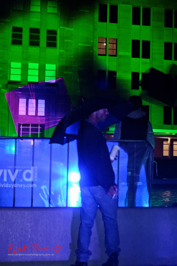 Man with umbrella and MCA bathed in green light - Vivid 2013