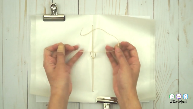 Two hands tying a double knot around the center string that makes up the spine of a DIY Traveler's Notebook Insert.
