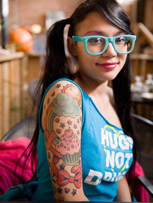 Vemos la imagen de una jovencita simpatica con gafas de pasta, lleva tatuajes en el brazo de golosinas y magdalenas